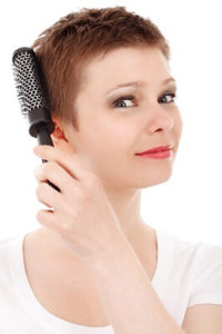 woman brushing hair 200x300 - Does Brushing or Washing Your Hair Affect Hair Loss? Read on for the Answers.